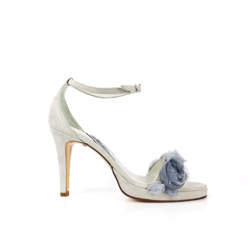 sandalias de novia adorno flores ante azul aguamarina cielo